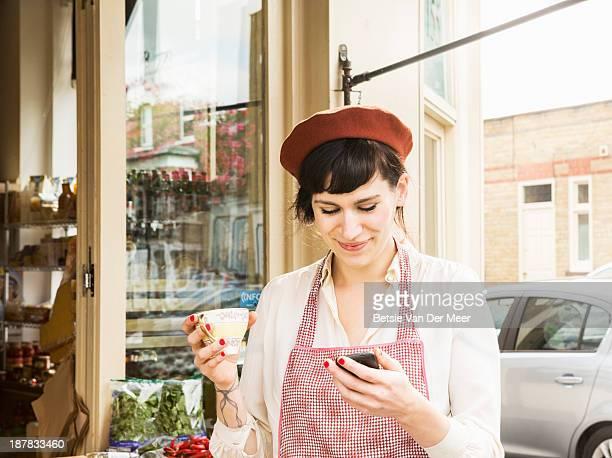 Shopkeeper checking phone while having a break.