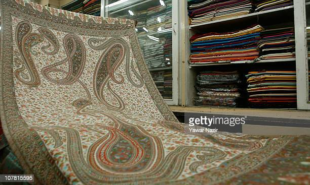 A shopkeeper displays a woven Kani or Jamewar shawl at his shop December 29 2010 in Srinagar the summer capital of Indian administered Kashmir India...