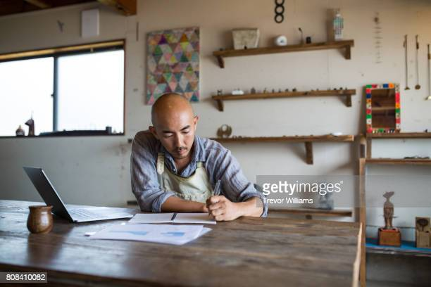 Shopkeeper doing his monthly financial planning and bookkeeping