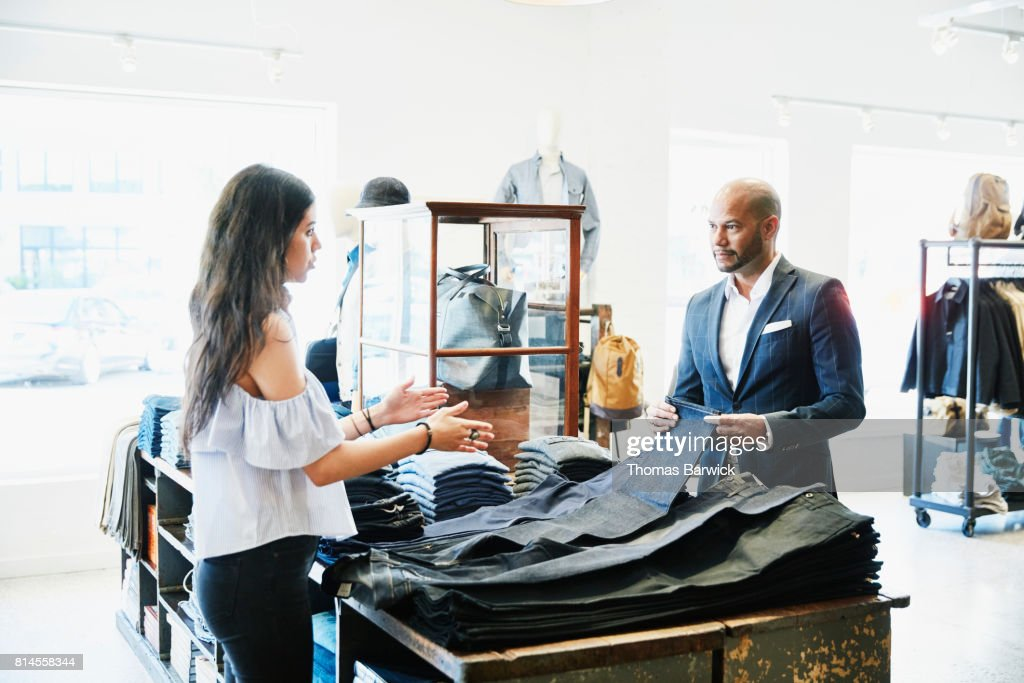 Shopkeeper explaining a selection of denim to customer in mens clothing boutique : Stock Photo