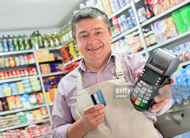 Shopkeeper holding a credit card machine