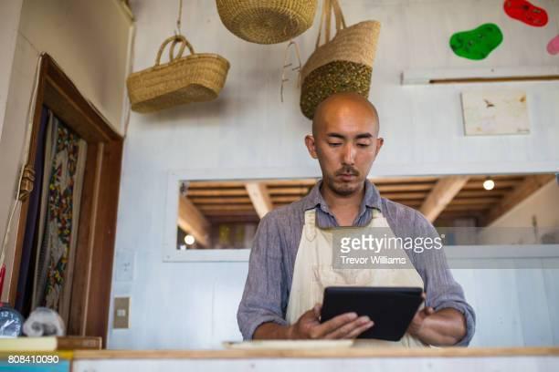 Shopkeeper holding a digital tablet