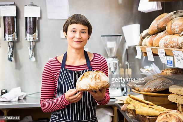 shopkeeper holding bread in bakery.