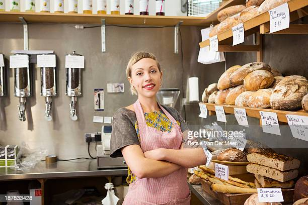 shopkeeper in front of bread display in shop.