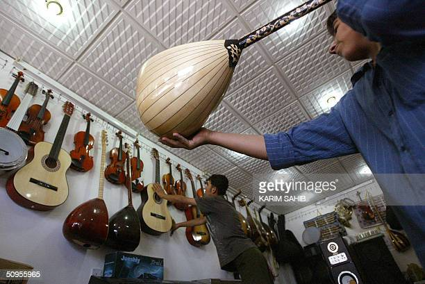 A shopkeeper lifts a Kurdish string instrument known as a Zambura in a music store in the northern Kurdish city of Suleimaniya 330 kms from Baghdad...