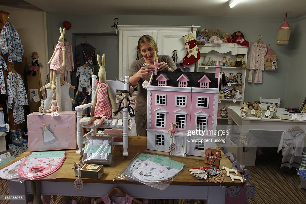 Shopkeeper Lisa Ayres arranges a display in her shop Cupboard Love which specialises in painted furniture and children's clothes in the rural town of Ludlow in Shropshire on December 8, 2011 in Ludlow, England. With a weak outlook at the start of the Christmas shopping boom, many retailers are slashing prices with the hopes of combating poor sales.