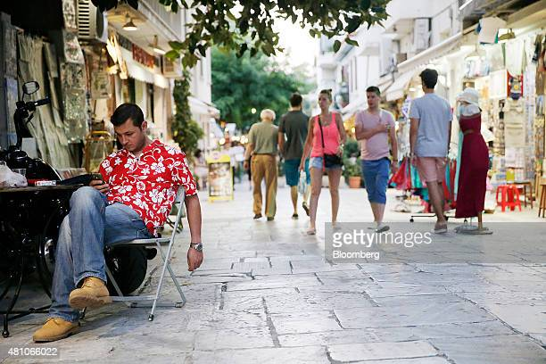 A shopkeeper looks at his smartphone while waiting for customers at his store in the Plaka tourist district of Athens Greece on Thursday July 16 2015...