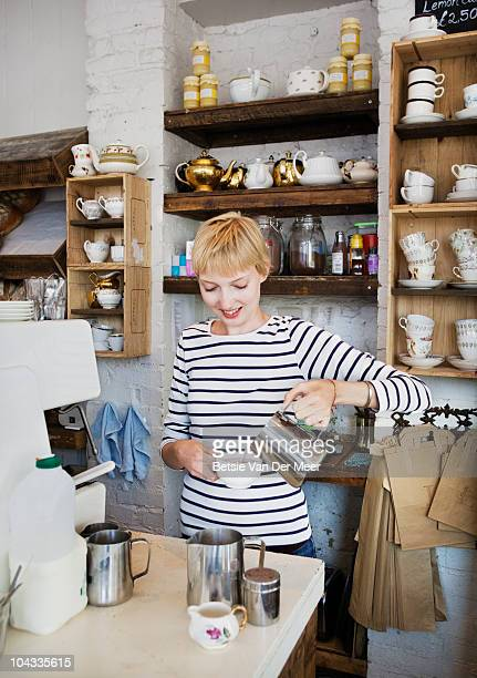 Shopkeeper making coffee behind counter.