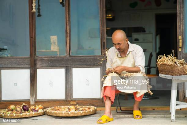 Shopkeeper or merchant sorting vegetables in front of his shop