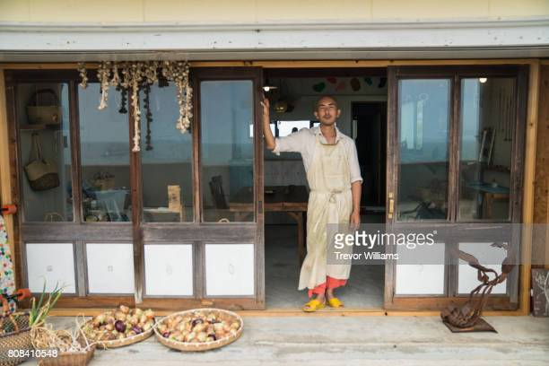 Shopkeeper or merchant standing in front of his shop
