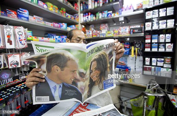 A shopkeeper reads a national newspaper giving news of the birth of a new royal baby in a convenience store in London on July 23 2013 International...