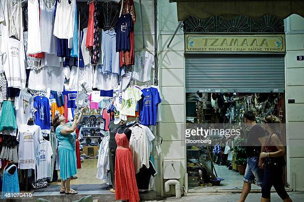 A shopkeeper removes a display of garments outside her store in preparation for closing time in the Plaka tourist district of Athens Greece on...