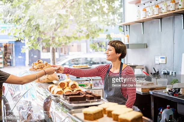 shopkeeper serving customer in delicatessen shop