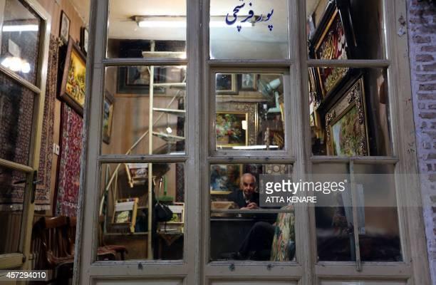 A shopkeeper sits in his carpet shop at the Bazaar in Tabriz in Iran's northwestern EastAzerbaijan province on October 15 2014 Tabriz Historic Bazaar...