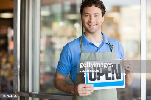 Shopkeeper smiling by storefront with open sign : Stock Photo