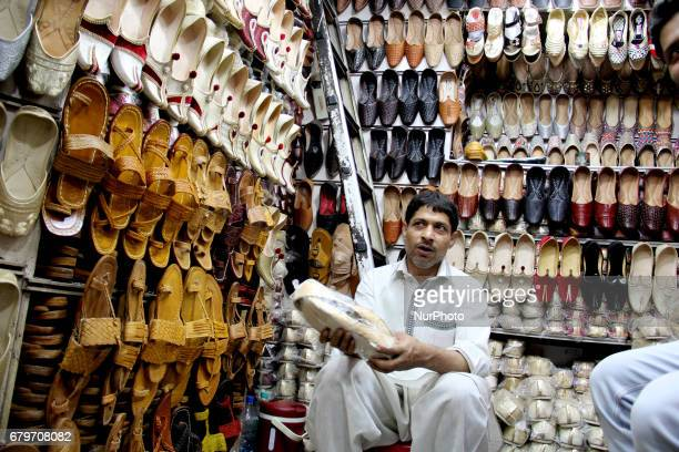 A Shopkeeper talks about the quality of the shoes to a customer in Old Delhi on May 6 2017