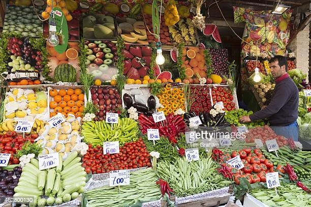 Shopkeeper with fresh fruit and vegetables with Turkish lira prices at food market Kadikoy Asian Istanbul Turkey#13#10