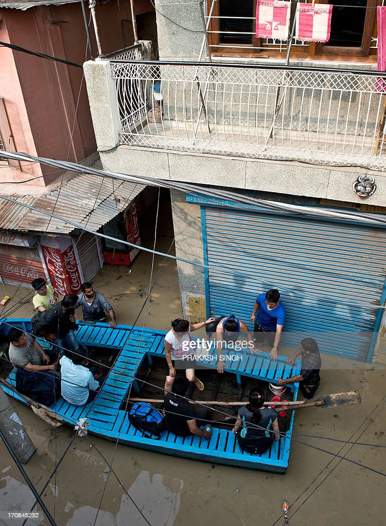 Shopkeepers and residents use a boat to traverse through the rising waters of the Yamuna River at the Tibetan market in New Delhi on June 19, 2013. Military helicopters dropped emergency supplies June 19 to thousands of tourists and pilgrims stranded by flash floods that tore through towns and temples in northern India, killing at least 138 people, officials said. AFP PHOTO/Prakash SINGH