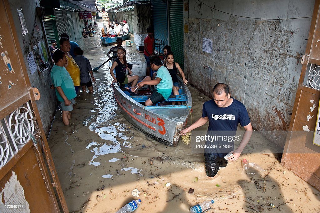 Shopkeepers and residents use boats to traverse through the rising waters of the Yamuna River at the Tibetan market in New Delhi on June 19, 2013. Military helicopters dropped emergency supplies June 19 to thousands of tourists and pilgrims stranded by flash floods that tore through towns and temples in northern India, killing at least 138 people, officials said. AFP PHOTO/Prakash SINGH