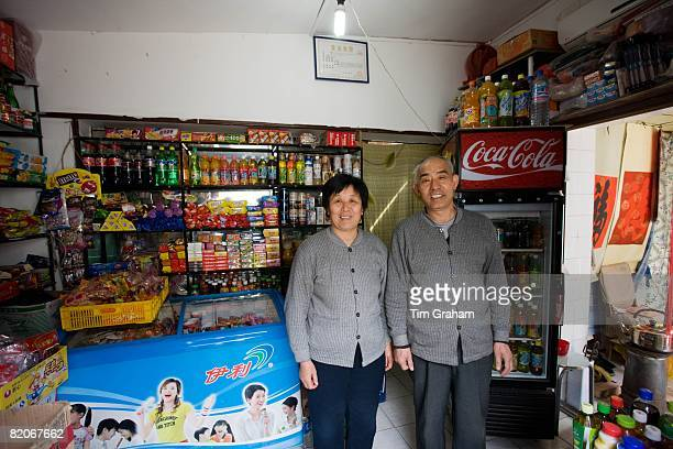 Shopkeepers in traditional shop for groceries sweets and drinks Hutongs Area Beijing China