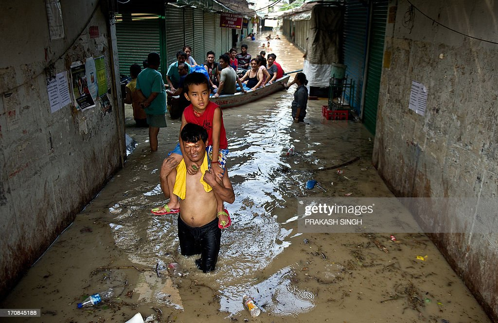 Shopkeepers make use of a boat as they wade through the rising waters of the Yamuna River at the Tibetan market in New Delhi on June 19, 2013. Military helicopters dropped emergency supplies June 19 to thousands of tourists and pilgrims stranded by flash floods that tore through towns and temples in northern India, killing at least 138 people, officials said. AFP PHOTO/Prakash SINGH