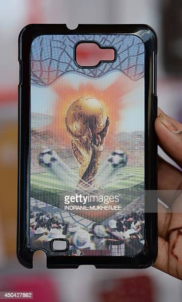 A shopowner holds a snapon mobile phone cover decorated with a 3D image of the FIFA World Cup trophy ahead of the forthcoming FIFA World Cup 2014 in...