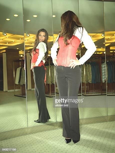 Shoppen Einkaufen Frau in einer Boutique probiert Mode vor dem Spiegel lady is shopping