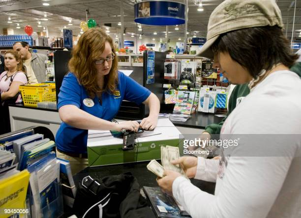 Shopper Aaron Lira right purchases a computer and DVDs from cashier Amanda Cox at the Best Buy store in Corpus Christi Texas US on on Friday Nov 27...