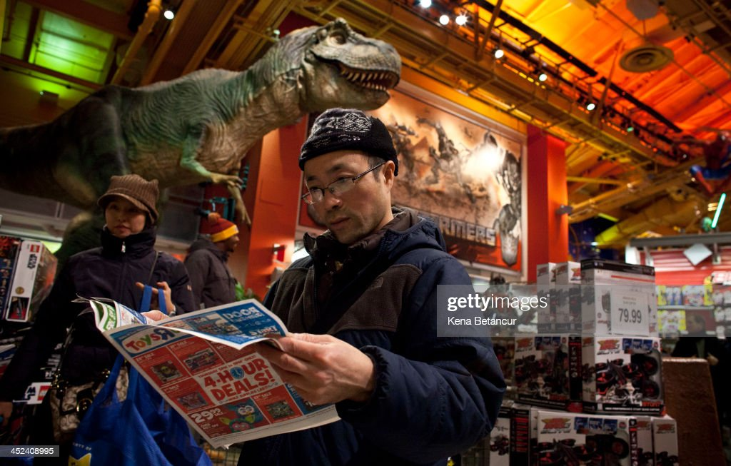 A shopper browses a sales circular inside Toys'R'Us in Times Square on November 28, 2013 in New York City. Black Friday shopping began early again this year with most major retailers opening their doors on Thanksgiving day.