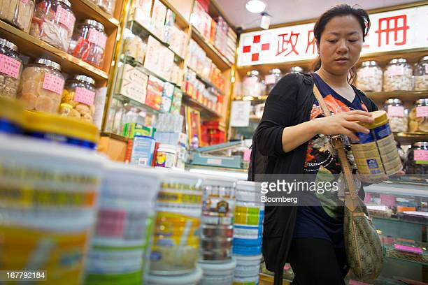 A shopper browses cans of baby formula displayed in a pharmacy in the Mongkok district of Hong Kong China on Tuesday April 30 2013 Financial...