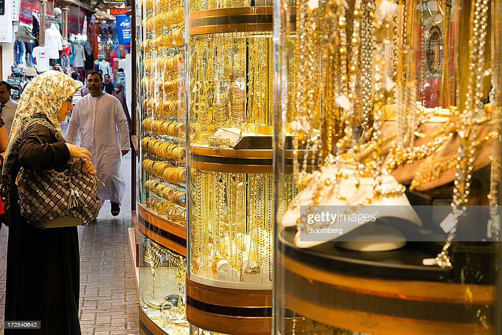 A shopper browses gold jewelry on display in the windows of a gold store in the Dubai Gold Souk in the Deira district of Dubai, United Arab Emirates, on Tuesday, July 2, 2013. Gold swung between gains and losses in London as investors weighed prospects for increased physical demand against a slowing stimulus in the U.S. Photographer: Duncan Chard/Bloomberg via Getty Images