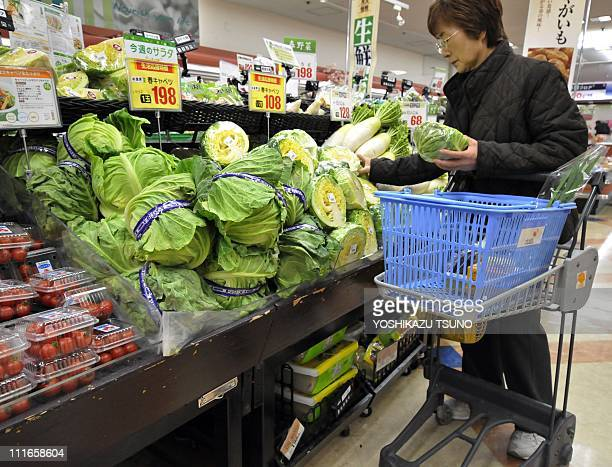 A shopper buys cabbages at a supermarket in Tokyo on April 5 2011 after the government ordered a halt to shipments of vegetables from Chiba...