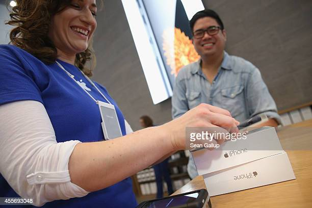 A shopper buys the new Apple iPhone 6 at the Apple Store on the first day of sales of the new phone in Germany on September 19 2014 in Berlin Germany...