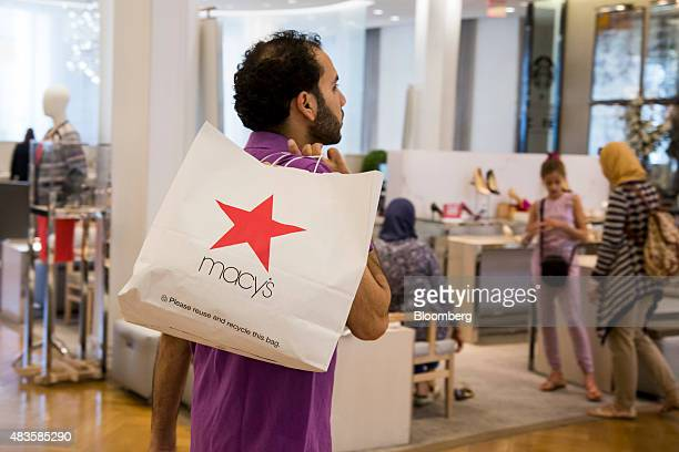 A shopper carries a bag at a Macy's Inc department store in New York US on Monday August 10 2015 Macy's Inc the largest US departmentstore company is...