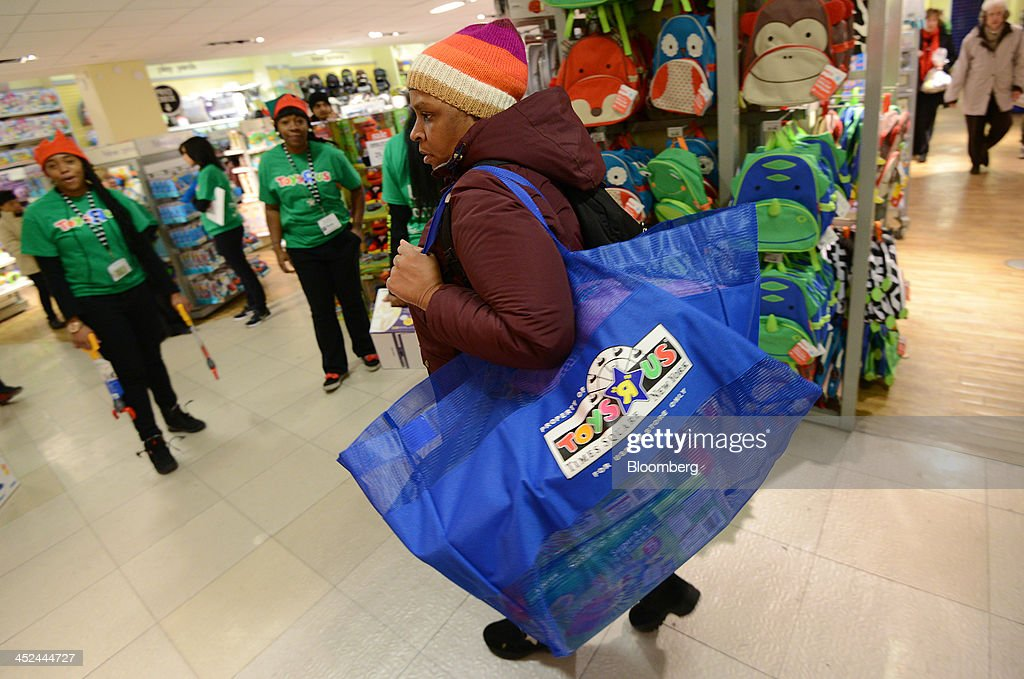 A shopper carries a bag filled with merchandise while walking through a Toys R Us Inc. store ahead of Black Friday in New York, U.S., on Thursday, Nov. 28, 2013. U.S. retailers will kick off holiday shopping earlier than ever this year as stores prepare to sell some discounted items at a loss in a battle for consumers. Photographer: Peter Foley/Bloomberg via Getty Images