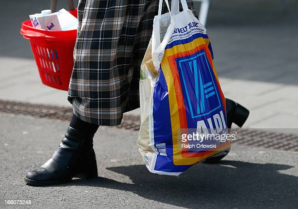A shopper carries a bag of groceries from an Aldi store on April 8 2013 in Frankfurt Germany Aldi which today is among the world's most successful...