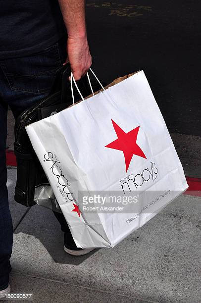 A shopper carries a bag of merchandise purchased in the Macy's department store in San Francisco's Union Square shopping district on October 4 2013...