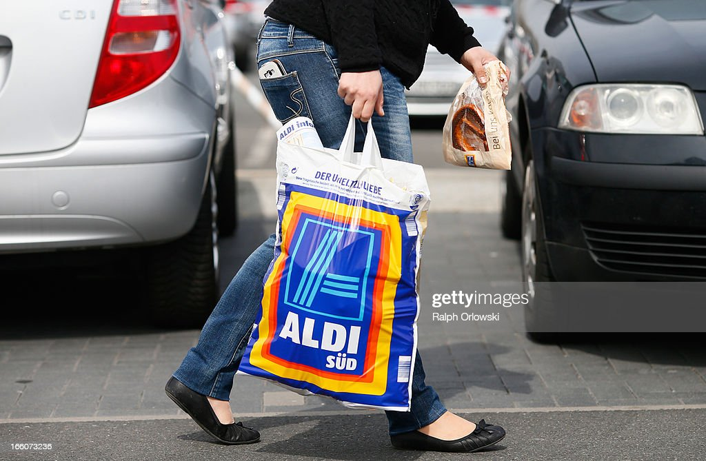 A shopper carries a bag outside an Aldi store on April 8, 2013 in Ruesselsheim near Frankfurt, Germany. Aldi, which today is among the world's most successful discount grocery store chains, will soon mark its 100th anniversary and traces its history back to Karl Albrecht, who began selling baked goods in Essen on April 10, 1913 and founded the Aldi name by shortening the phrase Albrecht Discount. His sons Karl Jr. and Theo expanded the chain dramatically, creating 300 stores by 1960 divided between northern and southern Germany, with Aldi Nord and Aldi Sued, respectively. Today the two chains have approximately 4,300 stores nationwide and have also expanded into other countries across Europe and the USA. Aldi Nord operates in the USA under the name Trader Joe's.