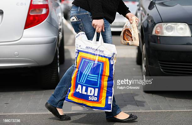 A shopper carries a bag outside an Aldi store on April 8 2013 in Ruesselsheim near Frankfurt Germany Aldi which today is among the world's most...