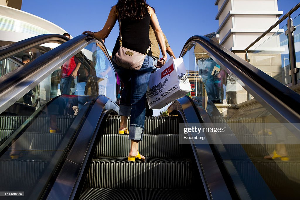 A shopper carries a Banana Republic LLC shopping bag while riding an escalator at the Fashion Valley Mall in San Diego, California, U.S., on Saturday, June 22, 2013. The Bureau of Economic Analysis is schedule to release personal consumption figures on June 26. Photographer: Sam Hodgson/Bloomberg via Getty Images