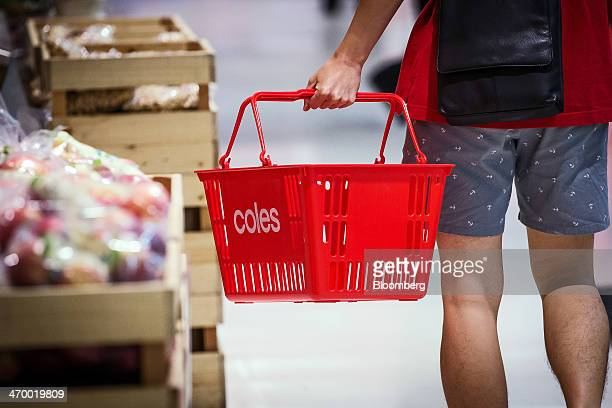 A shopper carries a basket while walking through a Coles supermarket operated by Wesfarmers Ltd in Sydney Australia on Tuesday Feb 18 2014 Wesfarmers...