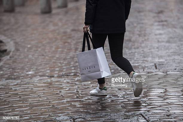 A shopper carries a branded shopping bag from a Sandro luxury clothing store operated by SMCP Group in Toulouse France on Wednesday Feb 10 2016...