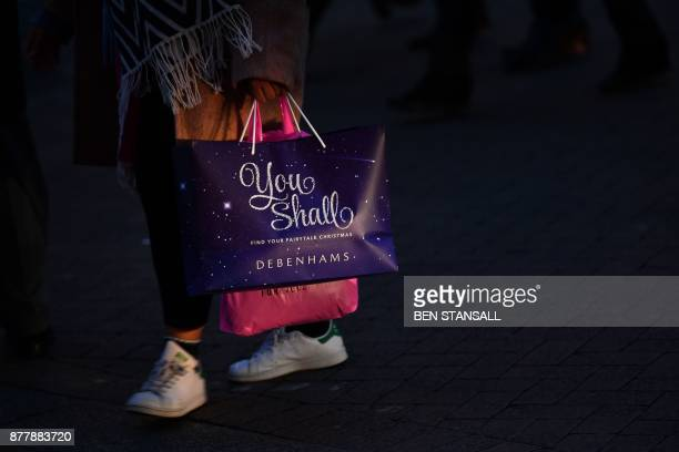 A shopper carries a Christmasthemed bag from the retailer Debenhams as they walk along Oxford Street in London on November 23 2017 Black Friday is a...