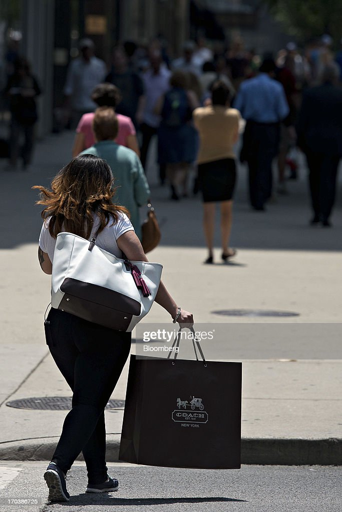 A shopper carries a Coach Inc. bag as she crosses the street in a retail area known as the 'Magnificent Mile' in Chicago, Illinois, U.S., on Tuesday, June 11, 2013. Sales at U.S. retailers probably rose in May as an improving job market gave consumers the confidence to shop for automobiles, home furnishings and clothing, economists said before reports this week. Photographer: Daniel Acker/Bloomberg via Getty Images