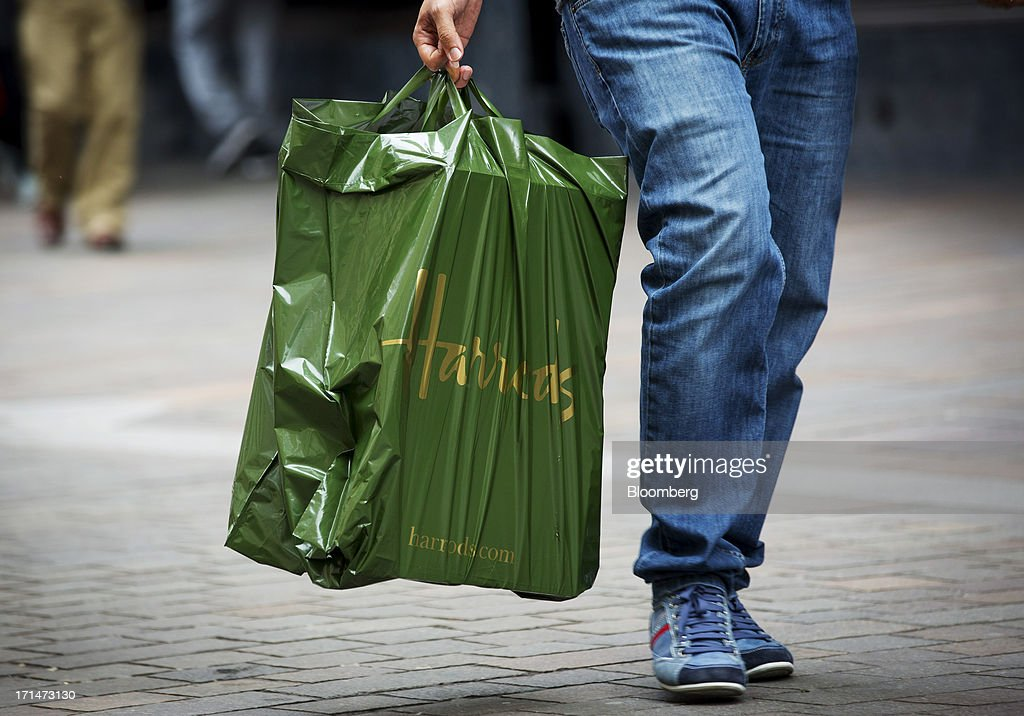 A shopper carries a Harrods branded carrier bag outside the luxury department store in London, U.K., on Monday, June 24, 2013. Harrods, which has more than 1 million square feet (90,000 square meters) of selling space, isn't concerned about the outlook for spending on luxury goods, Harrods Managing Director Michael Ward said. Photographer: Jason Alden/Bloomberg via Getty Images