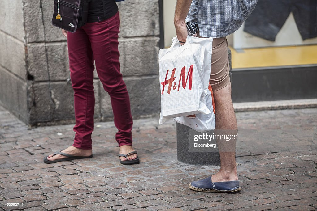 A shopper carries a Hennes & Mauritz AB (H&M) branded shopping bag in Toulouse, in Toulouse, France, on Tuesday, Aug. 12, 2014. The euro traded 0.3 percent from a nine-month low before reports this week that may show growth in the region weakened and inflation slowed, adding to signs the bloc's economy is struggling to recover. Photographer: Balint Porneczi/Bloomberg via Getty Images