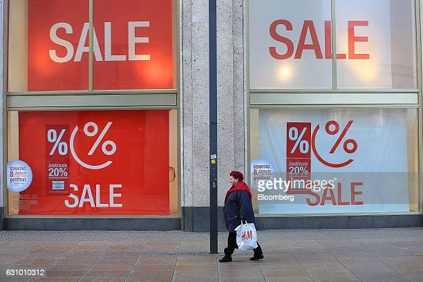 A shopper carries a Hennes Mauritz AB shopping bag as she passes a Galeria Kaufhof department store operated by Hudson's Bay Co as sales discount...