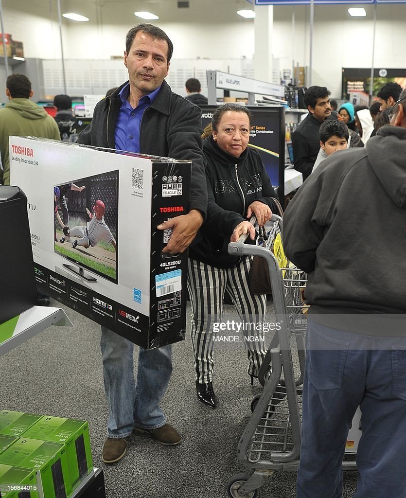 A shopper carries a large screen TV inside a Best Buy store which began their Black Friday sale at midnight on November 22, 2012 in Rockville, Maryland. Thanksgiving, the last US holiday undisturbed by mass commercialization, is now victim to the ever advancing Christmas shopping season, with stores welcoming shopaholics before the family turkey can be taken from the oven.