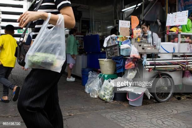 A shopper carries a plastic bag filled with takeaway food near a food stall in the Phaya Thai District of Bangkok Thailand on Wednesday April 5 2017...
