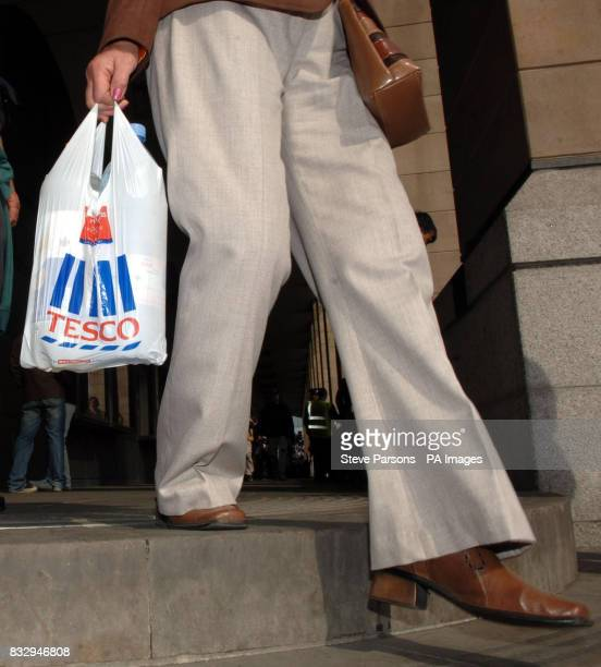 A shopper carries a Tesco bag in London on the day that the supermarket chain announced record profits of 255 billion